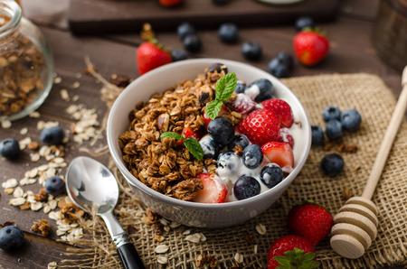 yaourt: Yogourt avec granola au four et les baies dans un bol petits, fraises, bleuets. Granola cuit avec des noix et de miel pour peu de douceur. Le yogourt maison