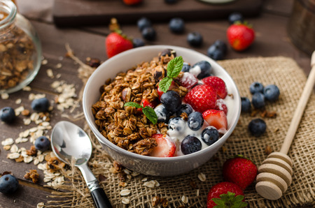 bowl: Yogurt with baked granola and berries in small bowl, strawberries, blueberries. Granola baked with nuts and honey for little sweetness. Homemade yogurt