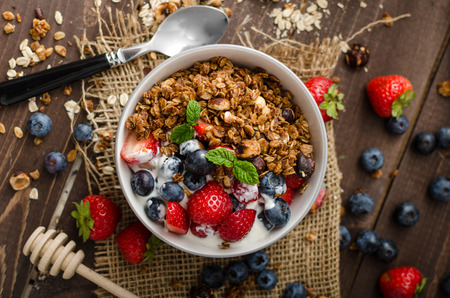 Yogurt with baked granola and berries in small bowl, strawberries, blueberries. Granola baked with nuts and honey for little sweetness. Homemade yogurt 版權商用圖片 - 43566749