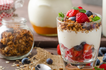 Yogurt with baked granola and berries in small glass, strawberries, blueberries. Granola baked with nuts and honey for little sweetness. Homemade yogurt
