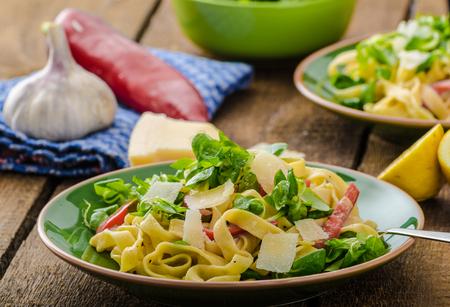 semolina pasta: Tagliatelle with bacon, garlic and salad, homemade pasta from best italian flour - semolina Stock Photo