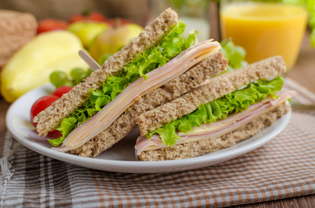Back to school sandwich, simple sandwich whole grain bread, salad, ham and cheese. Milk and fresh juice, fruit for bio healthy Stock Photo