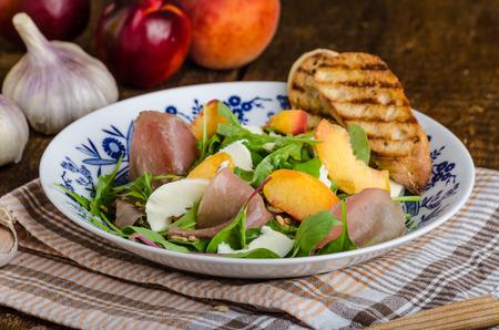 Rocket salad with prosciutto, mozzarella and peaches, panini baguette with bio garlic
