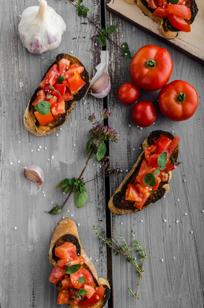 home grown: Bruschetta with tomatoes, garlic and herbs, czech delicious garlic home grown on bio garden, roasted in oven