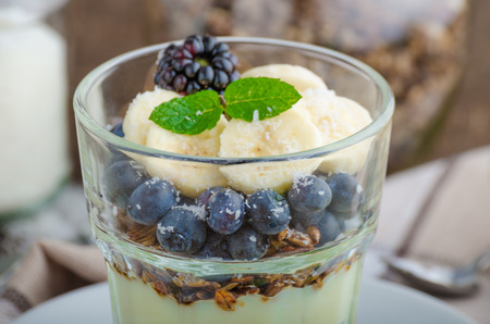 vanilla pudding: Vanilla pudding with berries and mint on wood desk