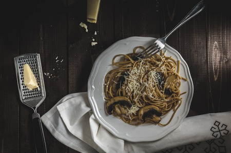 grain: Whole grain spaghetti with mushrooms and parmesan cheese, dark picture, focus on detail and darkness