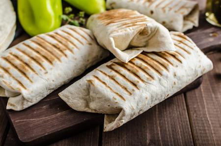 Ontbijt burrito op een houten bord en houten tafel, eieren, peper, aardappelen en vlees binnen