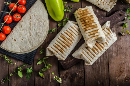 Breakfast burrito on wood board and wood table, eggs, pepper, potatoes and meat inside Standard-Bild