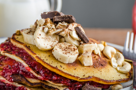 fresh graduate: Homemade pancakes with currant jam, banana and chocolate, roasted peanuts on top