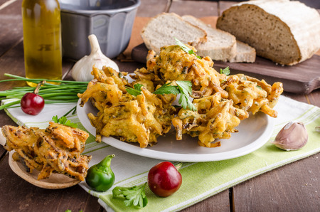 Crispy onion bhajis, delicious street food, with herbs and garlic
