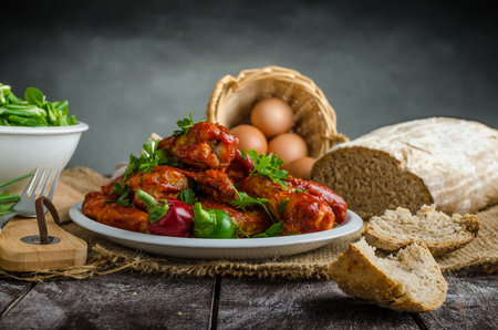 fresh graduate: Hot chicken wings with domestic bread from sourdough rye, little lamb lettuce salad, place for your text, advertising Stock Photo