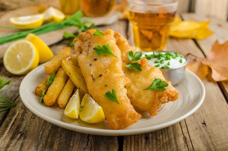 フィッシュ & チップス。ハーブのディップとビール、ビールねり粉に包まれた魚 写真素材