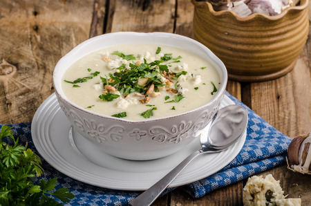Cauliflower soup with blue cheese, roasted nuts and herbs on top, ready for advertisnig, nice wooden board, old wood