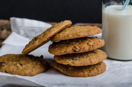 advertisment: Homemade Oatmeal Cream Pie cookies, with bio milk, black background for your advertisment, text
