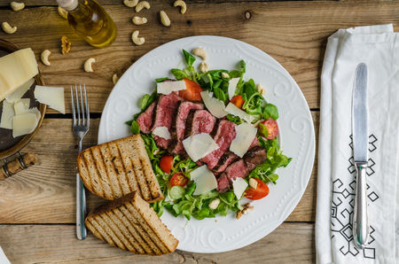 rump steak: Rump steak with spicy herb butter, nuts and little salad, sprinkled with parmesan and little panini bread