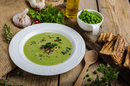 hot soup: Soup of young peas, with little garlic, roasted nuts and panini toasts Stock Photo