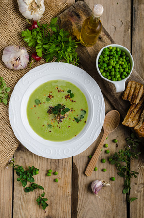 olive green: Soup of young peas, with little garlic, roasted nuts and panini toasts Stock Photo