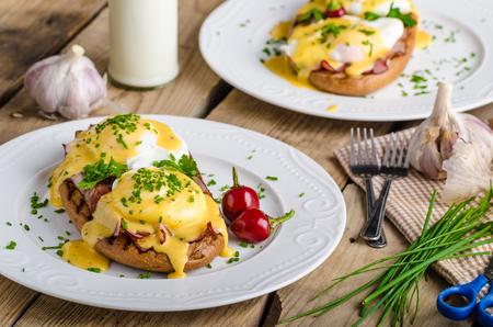 Eggs Benedict met kleine salade, melk en verse kruiden Stockfoto