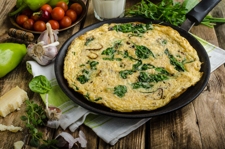 Frittata with spinach and garlic on wood board