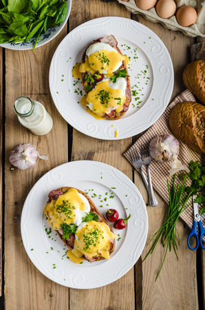 eggs and bacon: Eggs Benedict with little salad, milk and fresh herbs
