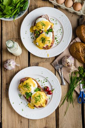huevo blanco: Huevos Benedict con poca ensalada, leche y hierbas frescas Foto de archivo