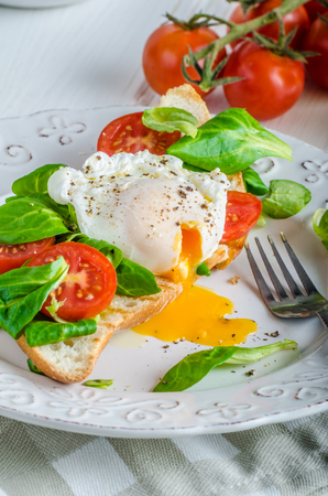 advertisment: Fresh Healthy Breakfast - poached egg on baguette with salad, tomato and olive oil, very simple and delicious, place for your advertisment