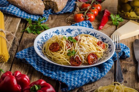 Italian pasta with roasted tomatoes and parmesan, rustic photo, whole table ingredience