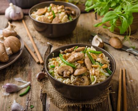 pollo frito: tallarines chinos con setas marrón, comida rápida sencilla y deliciosa. Foto de archivo