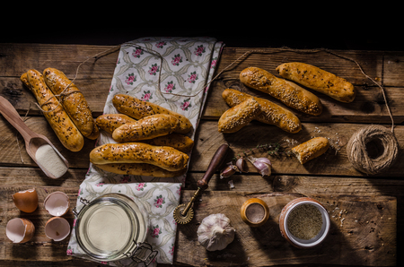 advertising text: Home-baked bread sticks sprinkled with sesame seeds and cumin, place for your advertising text