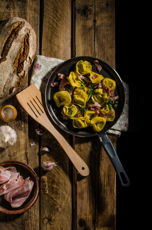 semolina pasta: Homemade tortellini pasta from semolina flour stuffed with cheese with roasted Italian ham, rustic photo for your advertising