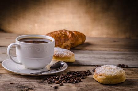 新鮮なコーヒーのコーヒー豆を新鮮なクロワッサン テーブルの上 写真素材