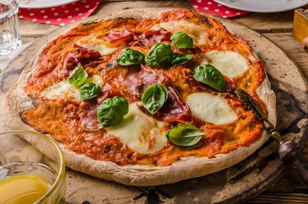 margherita: Rustic Italian pizza margherita with prosciutto and basil Stock Photo