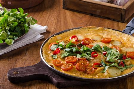 plato de comida: Frittata con los tomates, hierbas y chile, lechuga poco por dentro, muy simple, pero deliciosa comida