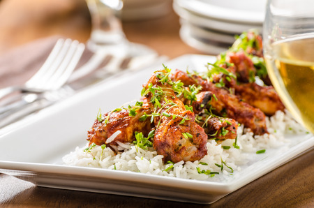 hot wings: Grilled chicken wings Hot wings with basmati rice, topped with microgreens Stock Photo