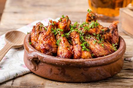 alas de pollo a la parrilla en Souce Sriracha hecho en casa, cubierto con los microgreens frescas, cerveza fresca detrás