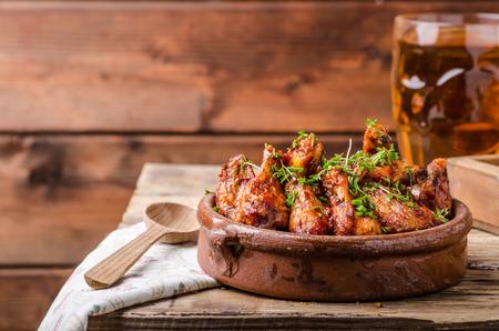 carne de pollo: alas de pollo a la parrilla en Souce Sriracha hecho en casa, cubierto con los microgreens frescas, cerveza fresca detr�s