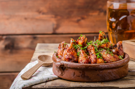 grill chicken: Grilled chicken wings in homemade Sriracha souce, topped with fresh microgreens, fresh beer behind Stock Photo