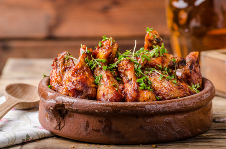Grilled chicken wings in homemade Sriracha souce, topped with fresh microgreens, fresh beer behind Stok Fotoğraf