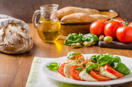 Caprese salade, heerlijke Italiaanse salade met mozzarela, basilicum, tomaten, verse olijfolie, op smaak met peper en zout