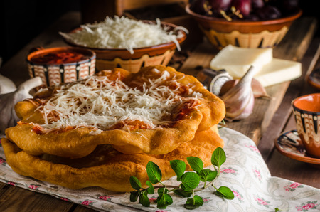 Traditional Langos are originally Hungarian fried pancakes made from yeast dough, topped with cheese, garlic and tomato ketchup. Archivio Fotografico