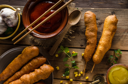 hot sauce: Delicious corndog - sausage coated in a thick layer of cornmeal batter on a stick, deep fried, with dijon mustard and sriracha hot sauce