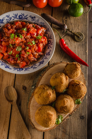 Delicious food consisting of chopped or shredded chicken meat, covered in dough, molded into a shape resembling a chicken leg, battered and fried, with hot salsa, rustic photo Stock Photo