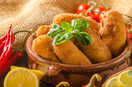 Chicken schnitzel and homemade potato croquettes with cheese and chilli Standard-Bild
