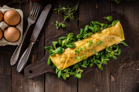 Franse omelet, pluizig, verse eieren en kruiden op een houten bord
