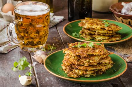 Aardappelpannenkoekjes met knoflook en kruiden, heerlijk Tsjechisch bier Stockfoto - 54353012