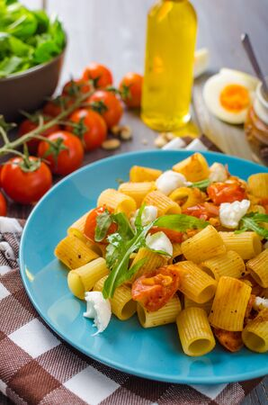 simple meal: Rigatoni pasta with mozzarella and tomato, fresh herbs on top, very simple and delicious meal Stock Photo