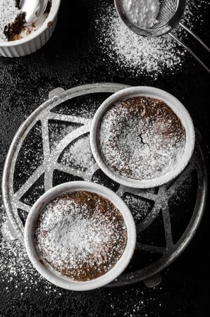 aphrodisiac: Chocolate souffle, simple photo on black background and table, topped with sugar Stock Photo
