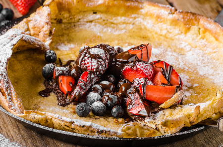 browned: Dutch Baby Pancakes with berries and chocolate, baked in oven on iron pan