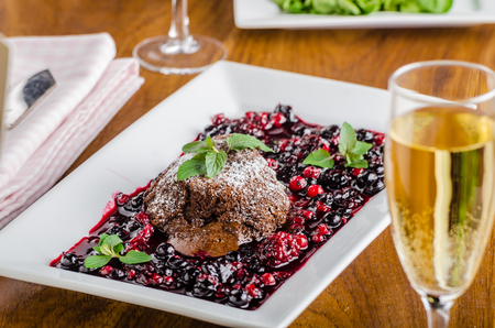 compostion: Chocolate souffle with forest fruit sauce and mint, restaurant compostion, glass of champagne wine