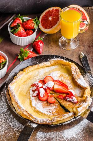 mini oven: Dutch baby pancake is delicious way to make pancake. Whole pancake is baked in oven on preheated iron skellet